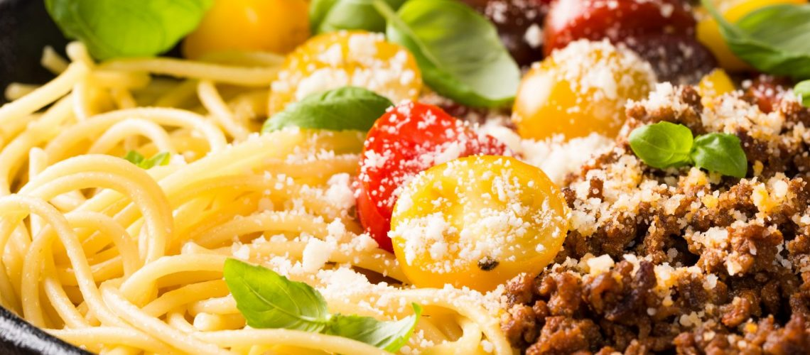 Delicious spaghetti Bolognaise or Bolognese with savory minced beef and cherry tomatoes garnished with parmesan cheese and basil in cost iron pan. Healthy italian food. Copy space.